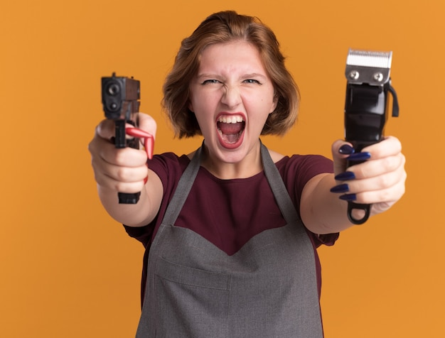 Молодая красивая женщина-парикмахер в фартуке, держащая триммер, нацеленная на пистолет, кричит с агрессивным выражением лица, стоя над оранжевой стеной