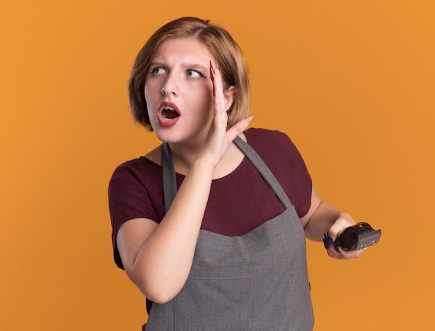 오렌지 벽 위에 서있는 입 근처 손으로 누군가에게 말하는 트리머를 들고 앞치마에 젊은 아름 다운 여자 미용사