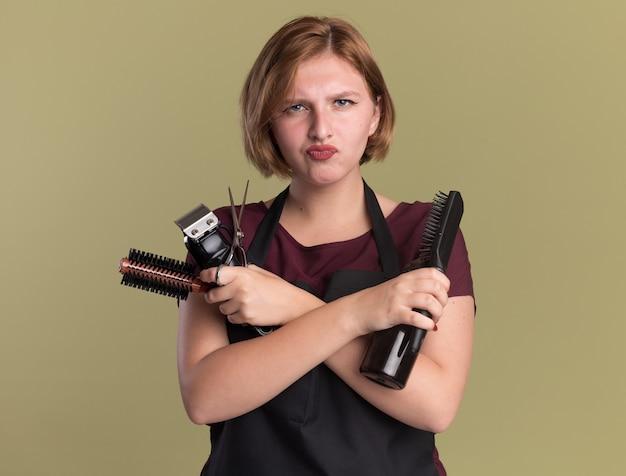 Молодая красивая женщина-парикмахер в фартуке, держащая триммер с щеткой для волос и распылителем, глядя вперед, недовольна скрещенными руками, стоя над зеленой стеной