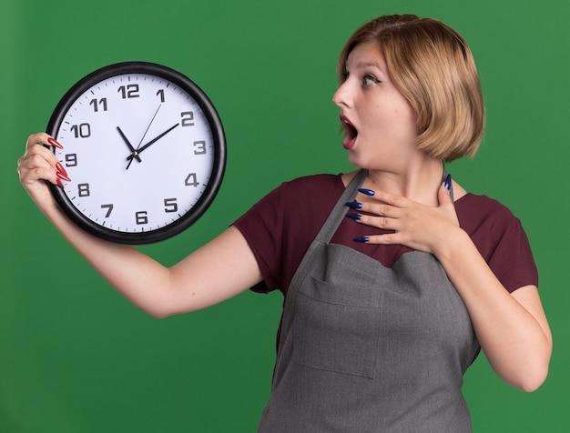 Молодая красивая женщина-парикмахер в фартуке, держащая настенные часы, глядя на нее, изумлен и удивлен, стоя над зеленой стеной