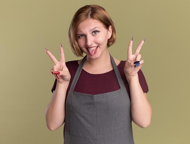 Молодая красивая женщина-парикмахер в фартуке, глядя на переднюю улыбку, высунув язык, показывая v-знак, стоящий над зеленой стеной