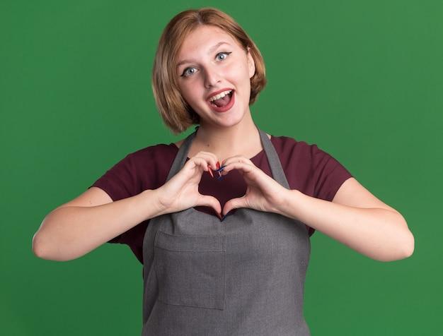 Молодая красивая женщина-парикмахер в фартуке, делая сердечный жест с пальцами, весело улыбаясь, стоя над зеленой стеной