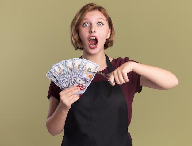 Молодая красивая женщина-парикмахер в фартуке показывает деньги, пытаясь разрезать деньги ножницами, эмоционально и взволнованно стоя над зеленой стеной