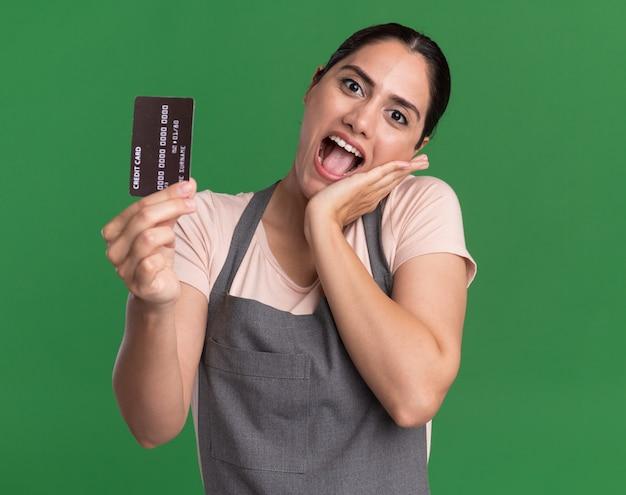 緑の壁の上に立って幸せで前向きな笑顔のクレジットカードを示すエプロンの若い美しい女性の美容師