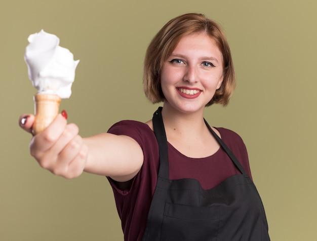 緑の壁の上に立っている顔に笑顔で正面を見てシェービングフォームとシェービングブラシを示すエプロンの若い美しい女性の美容師