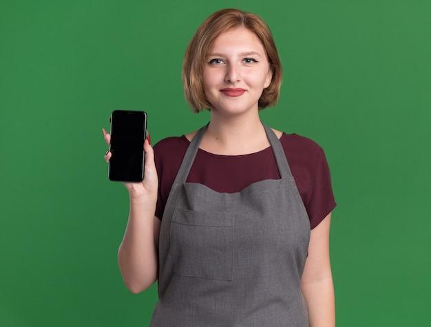 緑の壁の上に立って自信を持って笑顔のスマートフォンを示すエプロンの若い美しい女性の美容師