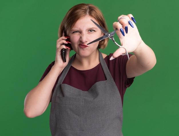エプロンで若い美しい女性の美容師が携帯電話で話している前にハサミが緑の壁の上に立って混乱して不快に見えることを示しています