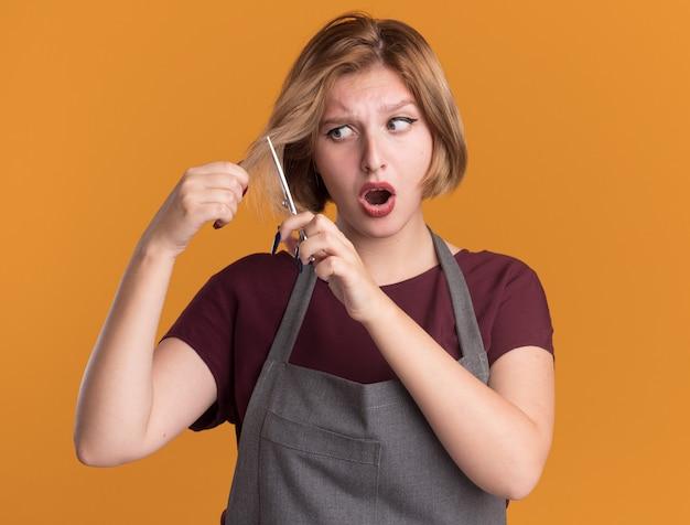 Молодая красивая женщина-парикмахер в фартуке пытается подстричь волосы ножницами и выглядит смущенной и удивленной, стоя у оранжевой стены