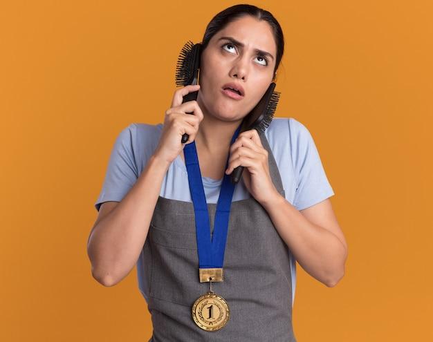 オレンジ色の壁の上に立って困惑して見上げるヘアブラシを保持している首の周りに金メダルを持つエプロンの若い美しい女性の美容師