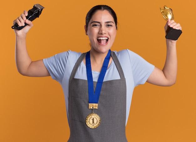 오렌지 벽 위에 행복하고 흥분 서 손을 올리는 트리머와 금 트로피를 들고 목 주위에 금메달과 앞치마에 젊은 아름 다운 여자 미용사