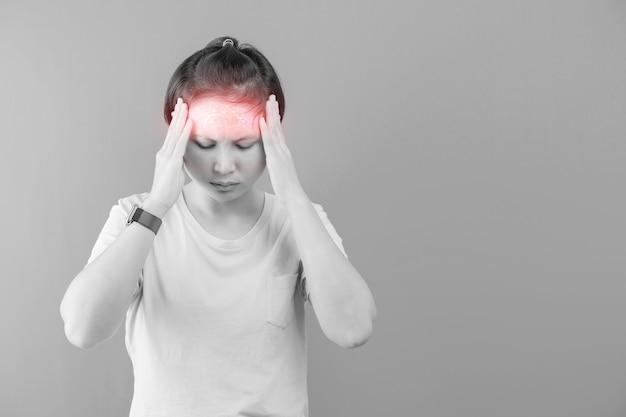 Молодая красивая женщина страдает головной болью, изолированной на сером фоне