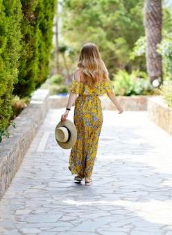 Young beautiful woman in a hat and maxi dress, sunny day, vacation, tropical nature, greece, crete island