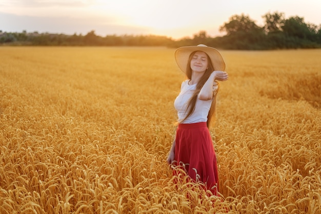 Young beautiful woman in hat standing among the stalks of ripe wheat. tranquility