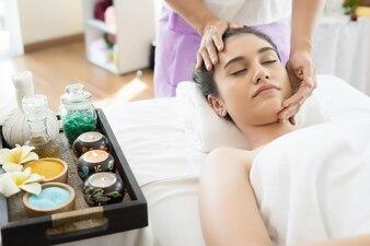 Young beautiful woman having face massage relaxing in spa.