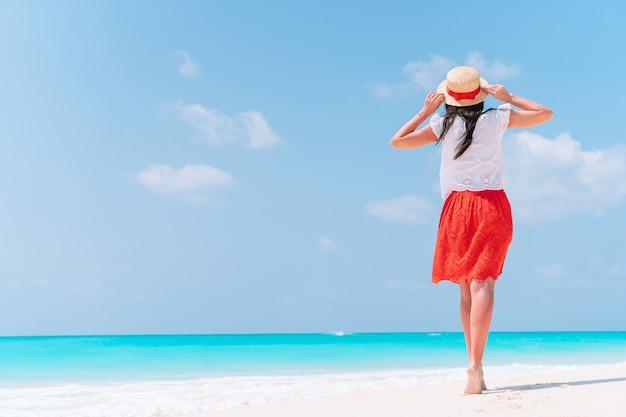 熱帯の海岸で楽しんでいる若い美しい女性。幸せな女の子の背景の青い空と海のターコイズブルーの水