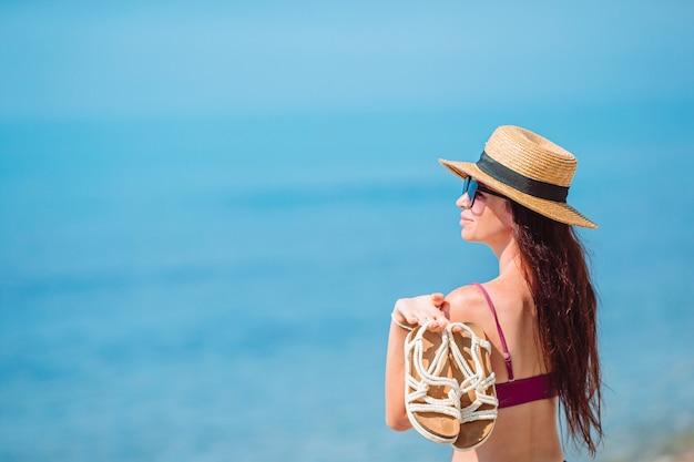 熱帯の海岸で楽しんで若い美しい女性。