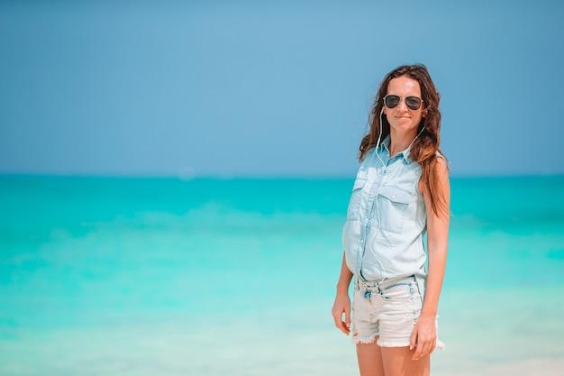 熱帯の海岸で楽しんでいる若い美しい女性