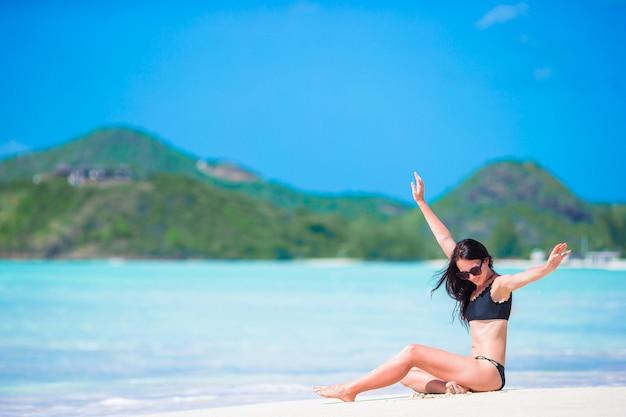 Young beautiful woman having fun on tropical seashore. happy girl on white sand tropical beach