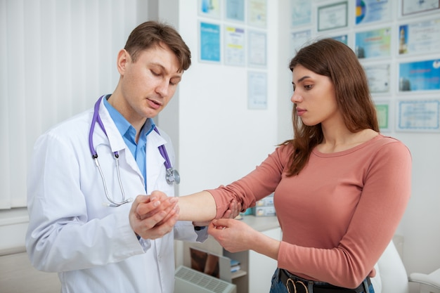 Young beautiful woman having her injured arm examined by experienced doctor at the hospital