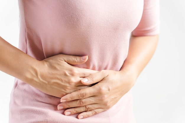 Young beautiful woman having painful stomachache on white. chronic gastritis. abdomen bloating concept.