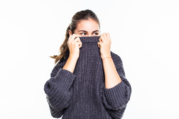 Young beautiful woman hiding face in red sweater dreamily looking in camera over white wall