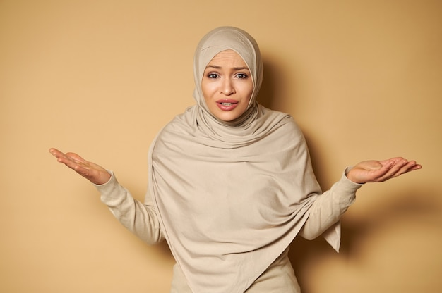 Young beautiful woman in hijab looks at the front expressing bewilderment