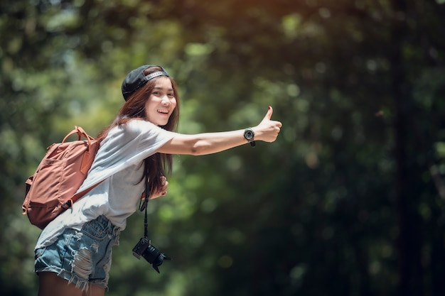 Young beautiful woman hitchhiking standing on road.