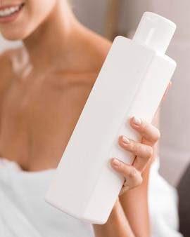 Молодая красивая женщина держит бутылку лосьона для тела