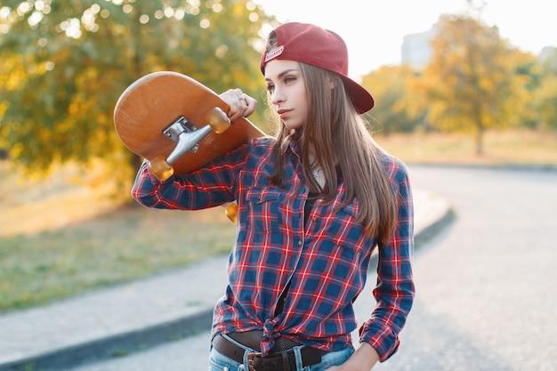 Молодая красивая женщина, держащая скейтборд в парке на закате