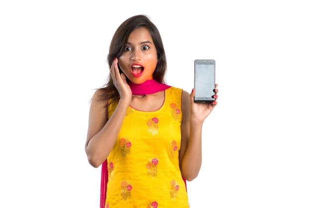 들고 빈 화면 스마트 폰 또는 모바일 또는 태블릿 전화를 보여주는 젊은 아름 다운 여자