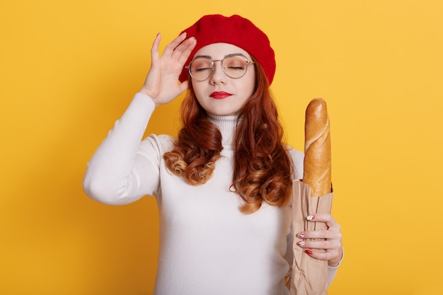 Young beautiful woman holding bag of fresh baguette on yellow