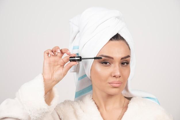 Young beautiful woman holding a black mascara .