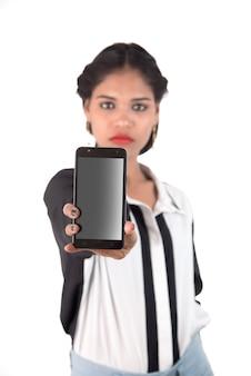 Молодая красивая женщина, держащая пустой экран смарт-телефона на белом фоне