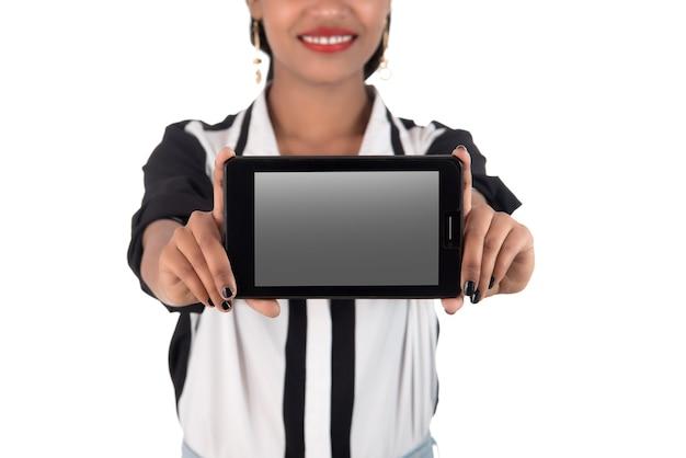 흰 벽에 빈 화면이 스마트 폰을 들고 젊은 아름 다운 여자
