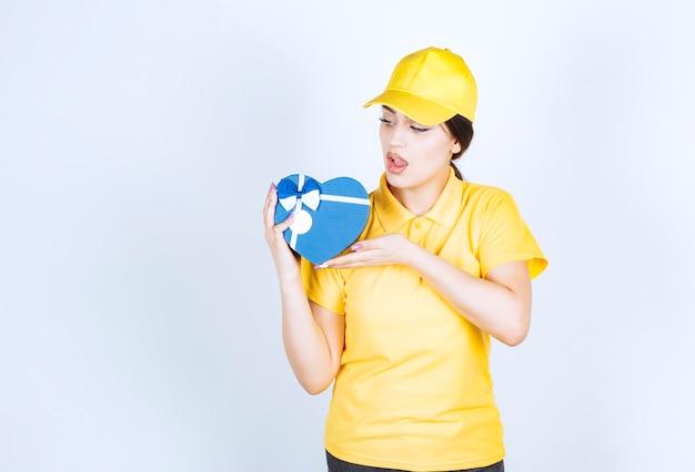 Giovane bella donna che tiene scatola blu a forma di cuore su un muro bianco