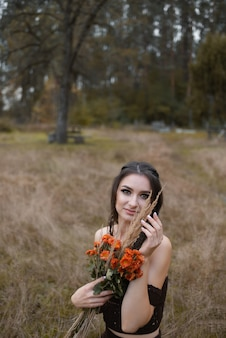 Young beautiful woman holding a bouquet of chrysanthemum flowers in a field looking at the camera