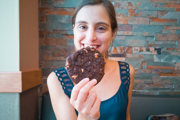 Young beautiful woman holding a chocolate cookie