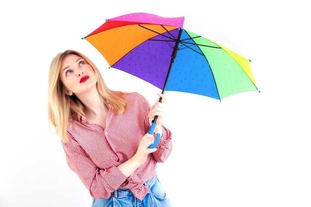 白い背景の上の色の傘を保持している若い美しい女性