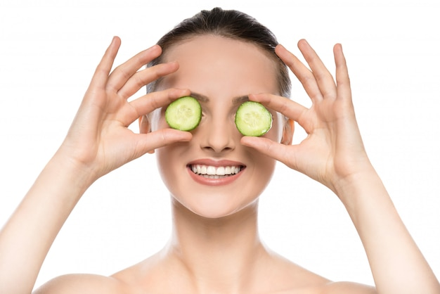 Young beautiful woman holding cucumber slices on the face.