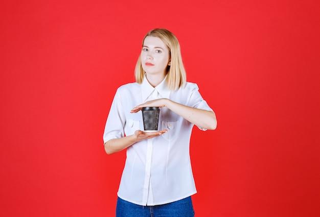Молодая красивая женщина, держащая ее кофе обеими руками