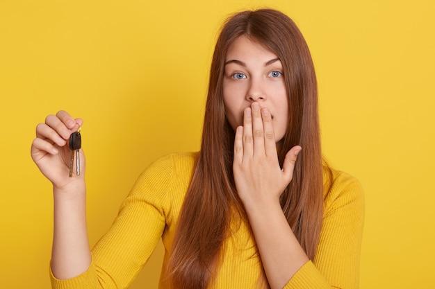黄色のホームキーを保持している若い美しい女性