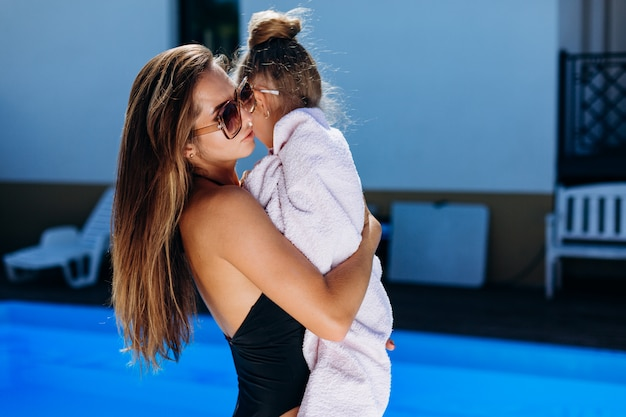 Young beautiful woman holding a little girl in a towel by the pool