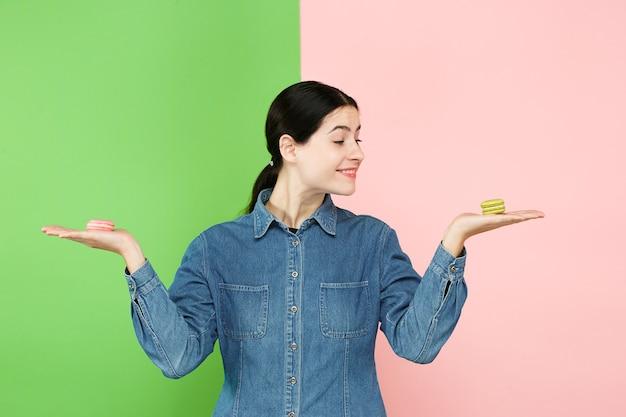 スタジオでトレンディな色付きの背景の上に彼女の手でマカロン菓子を保持している若い美しい女性。