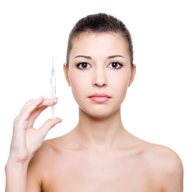 Young beautiful woman holding medical syringe in hand