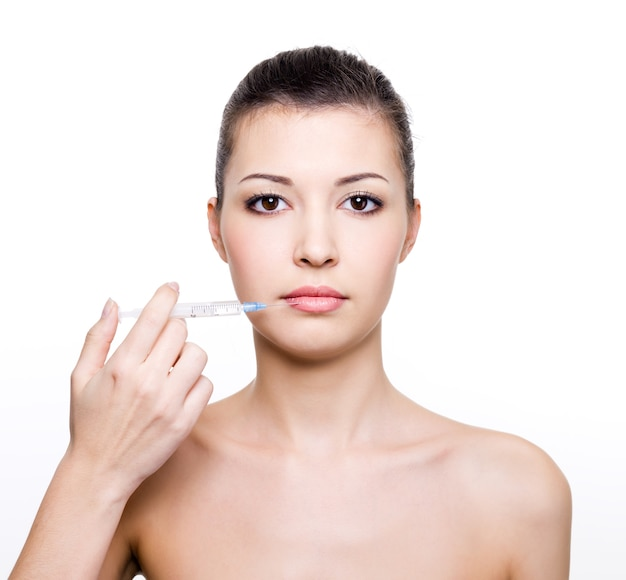 Young beautiful woman holding medical syringe near the lips