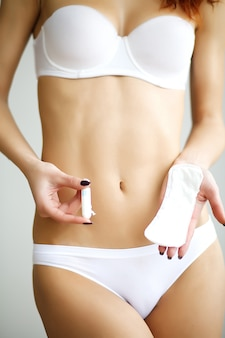 Young beautiful woman holding a menstruation cotton tampon and gasket in her hand, in white underwear