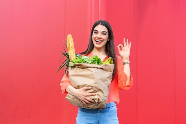Молодая красивая женщина, держащая бумажный пакет продуктов из супермаркета с счастливым лицом, показывая знак ок, стоя и улыбается с уверенной улыбкой