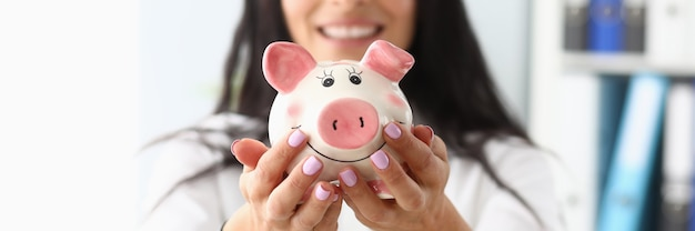 Young beautiful woman holding piggy bank in form of pig in hands