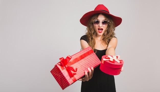 Giovane bella donna che tiene i regali, vestito nero, cappello rosso, occhiali da sole, felice, sorridente, sexy, elegante, scatole regalo, celebrando, positivo, emotivo