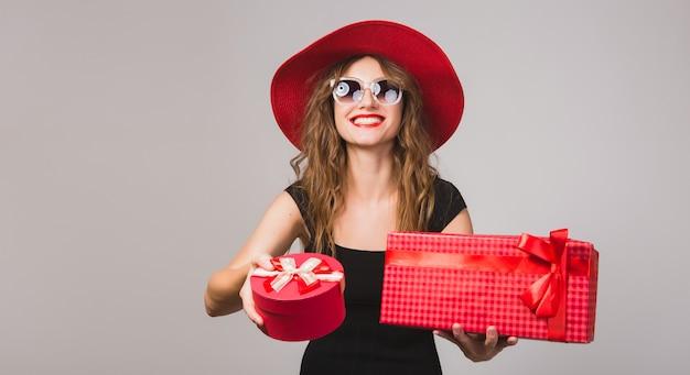 プレゼント、黒のドレス、赤い帽子、サングラス、幸せ、笑顔、セクシー、エレガント、ギフトボックス、祝う、肯定的、感情的な若い美しい女性
